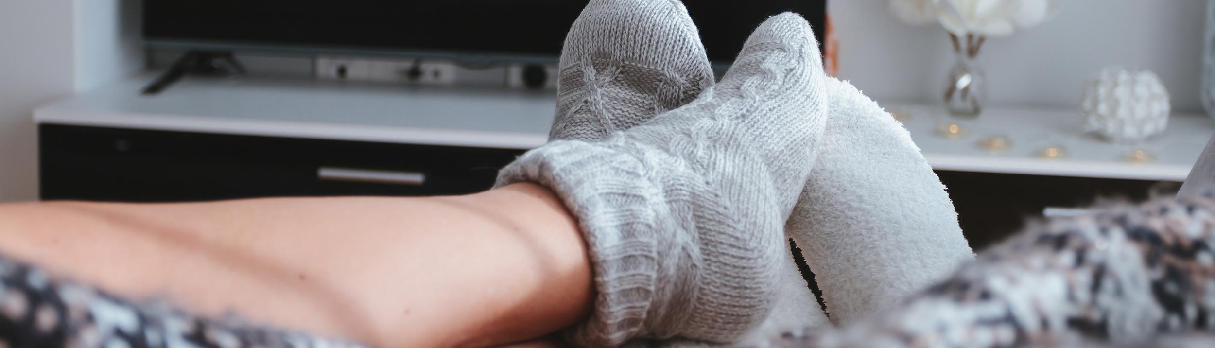 Ein Paar entspannt auf dem Sofa. Dank Heizungen der Firma Haesler AG wird Ihr Zuhause wohlig warm.