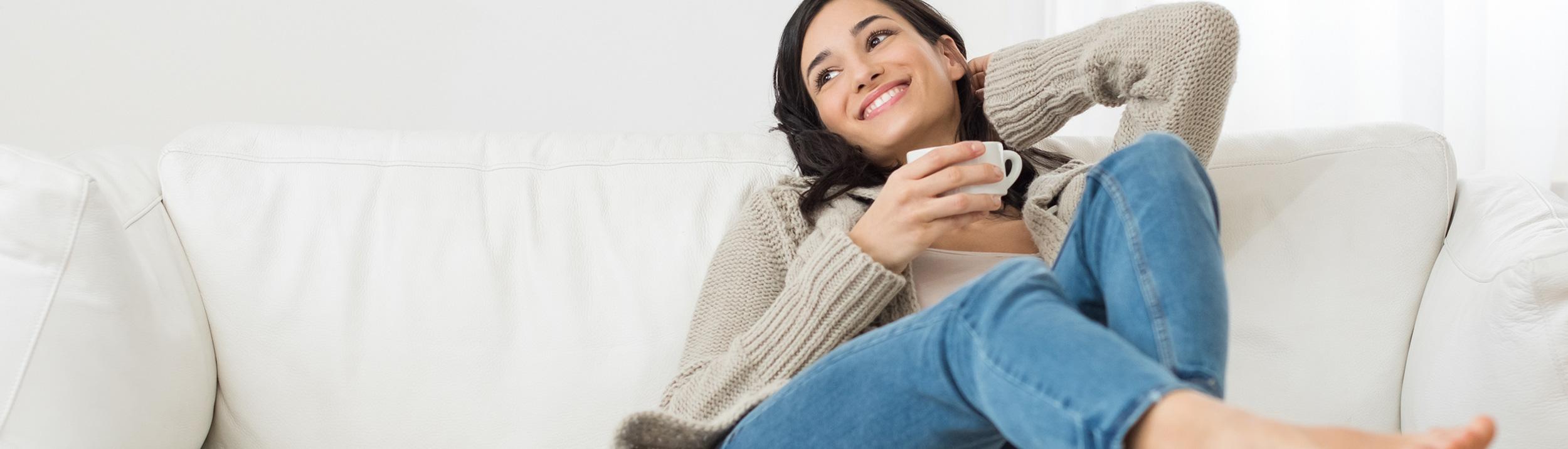 Eine Frau entspannt auf dem Sofa und trinkt einen Kaffee. Gemütlich warmes Zuhause dank Heizungen der Firma Haesler AG.