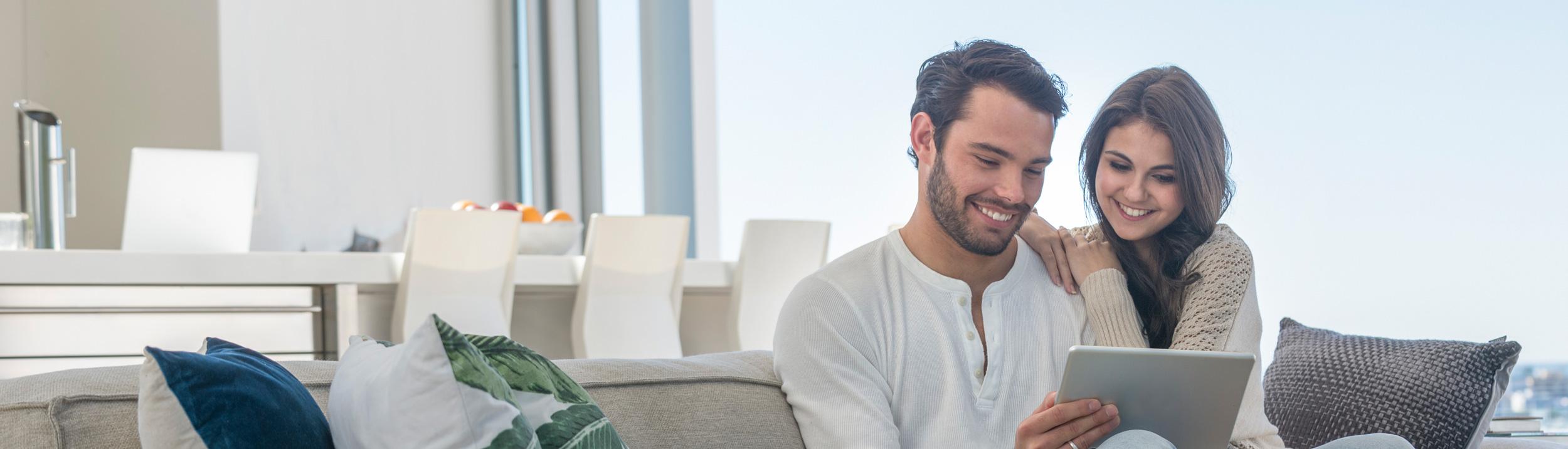 Ein Paar sitzt auf dem Sofa, schaut auf ein Tablett und lächelt. Wohliges Zuhause dank Heizungen der Firma Haesler AG.